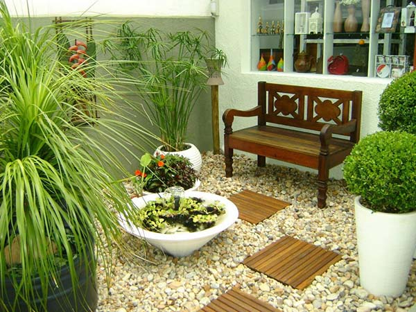 a little garden features a wooden bench and water accents
